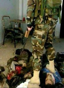 Der kurdische Peshmerga steht stolz auf einem Leichenberg.