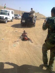 Eine Leiche eines ISIS-Terroristen wird von Peshmergas durch die Gegend geschleift.